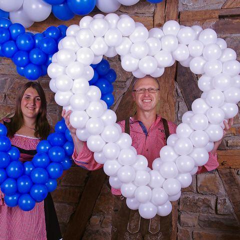 Easy-Fix-Herz aus Luftballons. Auf easy-Fix-Gestänge aufgezogene Ballons in weiß mit Personen im Hintergrund