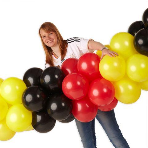 Luftballongirlande in schwarz, gelb rot mit Person