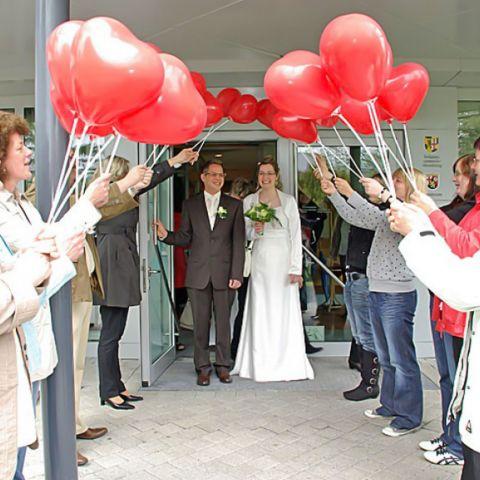 Das Brautpaar kommt aus dem Standesamt und die Freunde bilden ein Spalier mit Herzballons.